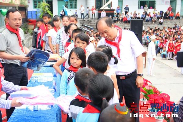 邓启鹏/图为县长邓启鹏向贫困生及留守儿童赠送书包和文具的情景